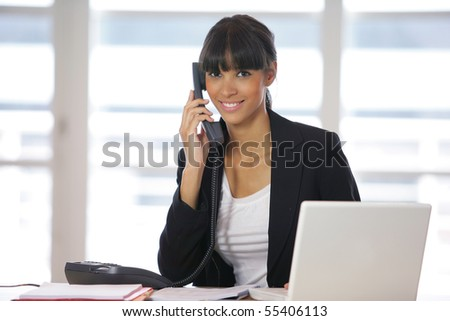 Portrait of a young woman on phone in front of a laptop computer - stock photo