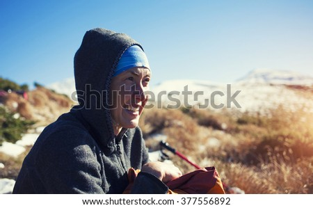 Portrait of a young woman on the sky background and snowy mountains.