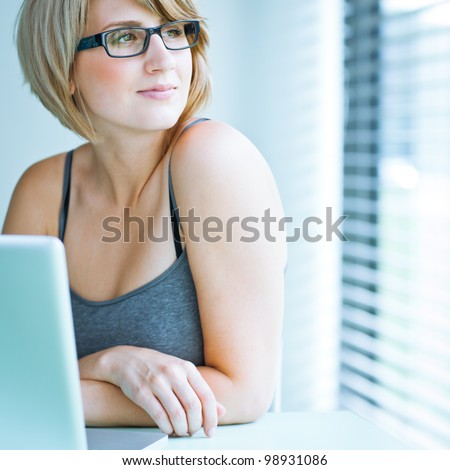 Portrait of a young woman pensively looking out of the window while sitting in front of her laptop - stock photo