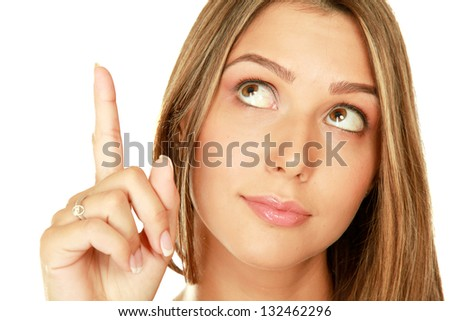 Portrait of a young woman pointing up - stock photo