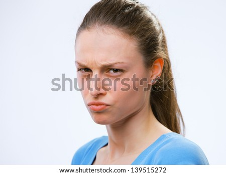 Portrait of a young woman scowling at you - stock photo