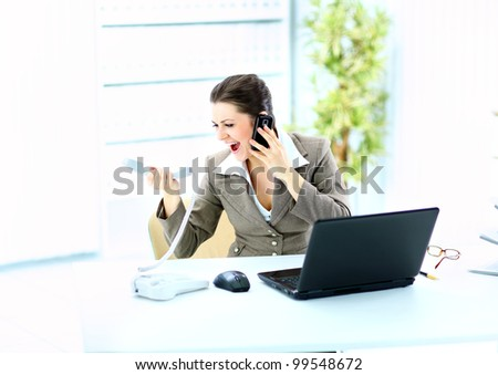 Portrait of a young woman shouting in phone in front of a laptop computer - stock photo