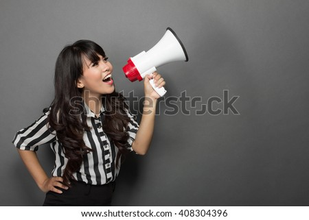 portrait of a young woman shouting with a megaphone against grey background - stock photo