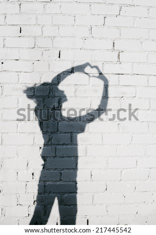 Portrait of a young woman showing a Heart with Her Hands around on the brick wall background. Photo of shadows of girl - stock photo