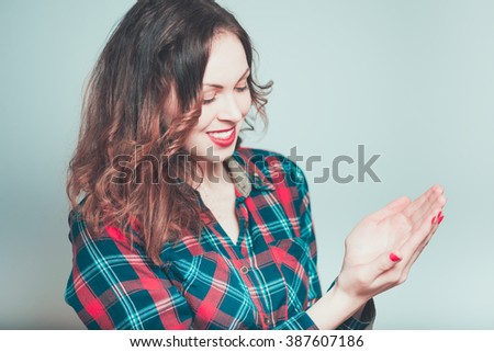 Portrait of a young woman showing something on the palm isolated on a gray background - stock photo