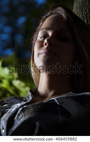 portrait of a young woman sitting in a tree