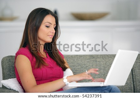 Portrait of a young woman sitting on a sofa with a laptop computer - stock photo