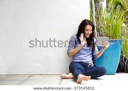 Portrait of a young woman sitting on floor using digital tablet and waving hello on chat