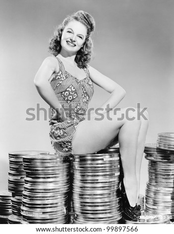 Portrait of a young woman sitting on stacks of film canisters - stock photo