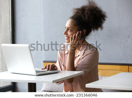 Portrait of a young woman smiling and talking on mobile phone at office - stock photo
