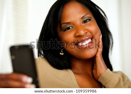 Portrait of a young woman smiling at you while sending a text message by the cellphone - stock photo