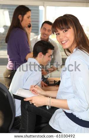 Portrait of a young woman smiling in office - stock photo