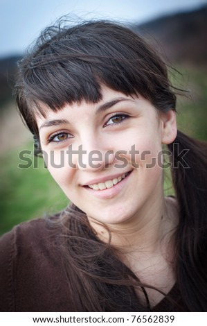 Portrait of a young woman smiling outdoors