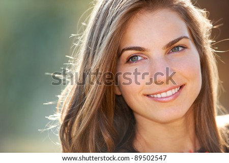 Portrait of a young woman smiling while outdoor in the sun. - stock photo