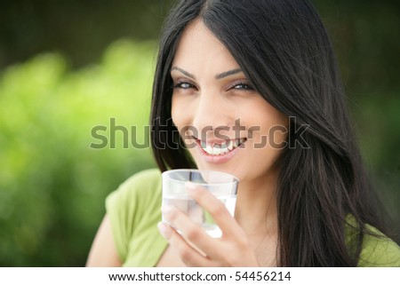 Portrait of a young woman smiling with a glass of water - stock photo