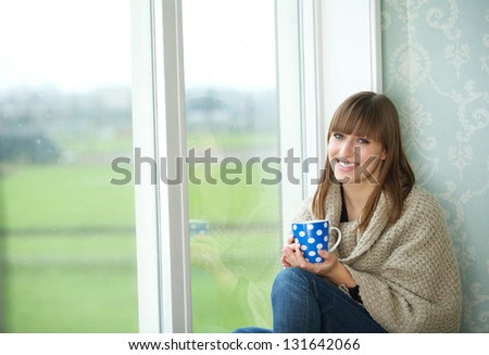 Portrait of a young woman smiling with tea cup next to window - stock photo