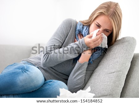 Portrait of a young woman sneezing In to tissue - stock photo