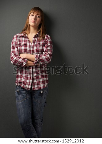 Portrait of a young woman standing alone with arms crossed - stock photo