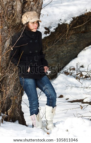 Portrait of a young woman standing in snowy winter forest, wearing a cap, black coat, jeans, white boots, standing by a tree, looking away - stock photo