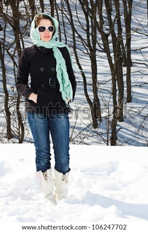 Portrait of a young woman standing in snowy winter forest, wearing scarf on her head, black coat, jeans, white boots, sunglasses - stock photo