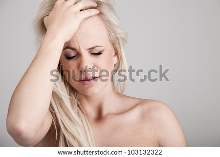 Portrait of a young woman suffering from headache on background