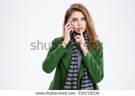 Portrait of a young woman talking on the phone and showing finger over lips isolated on a white background - stock photo