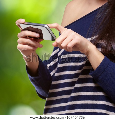 portrait of a young woman touching a modern mobile against a nature background - stock photo