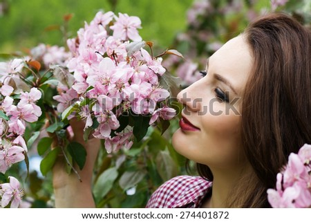 Portrait of a young woman touching flowers on tree. - stock photo