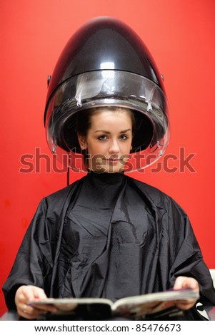 Portrait of a young woman under a hairdressing machine while looking at the camera
