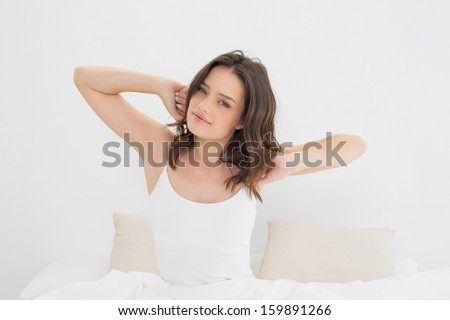 Portrait of a young woman waking up in bed and stretching her arms - stock photo