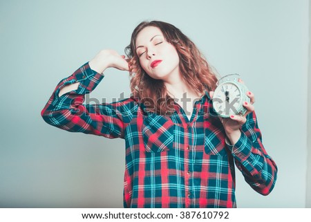 Portrait of a young woman wants to sleep with the alarm clock, isolated on a gray background - stock photo