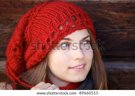 Portrait of a young woman wearing a red hat against a wooden wall. - stock photo