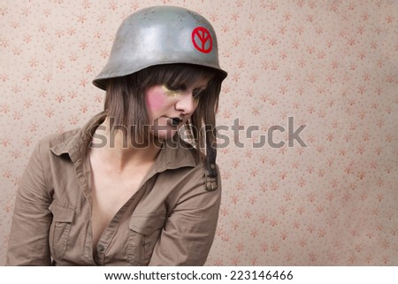 portrait of a young woman wearing  an artistic makeup and a second world  war army hat, with a  vintage background - stock photo