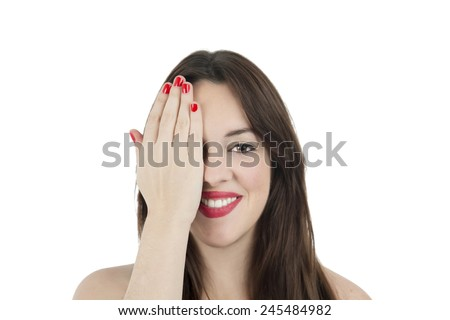Portrait of a young woman wearing red lipstick and covering one eye with her hand against a white background - stock photo