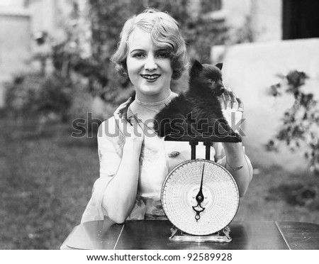 Portrait of a young woman weighing her puppy on a weighing scale - stock photo