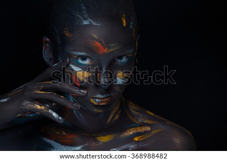 Portrait of a young woman who is posing covered with black paint in the studio on a black background