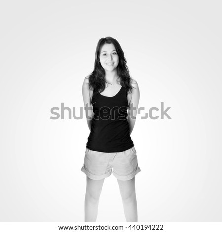Portrait of a young woman with a beautiful smiling face, she's wearing shorts and a black top in front of bright background, black and white photo  - stock photo