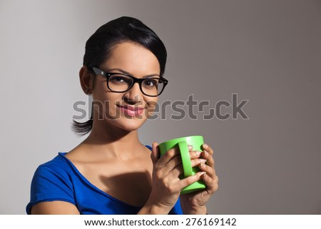Portrait of a young woman with a mug of tea - stock photo