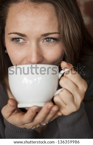Portrait of a young woman with a white coffee cup looking directly at the camera - stock photo