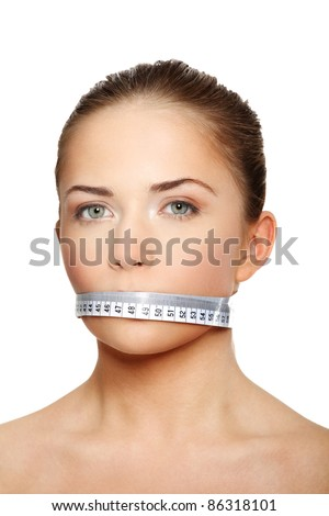 Portrait of a young woman with a white measuring tape covering the mouth - stock photo