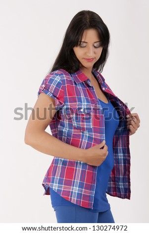 Portrait of a young woman with black hair, checked blouse, blue top and trousers / stylish Woman - stock photo