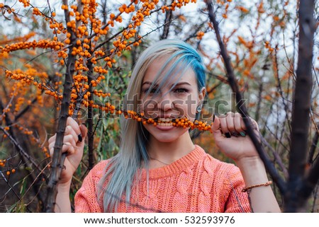 Portrait of a young woman with blue hair with a branch of sea-buckthorn in teeth