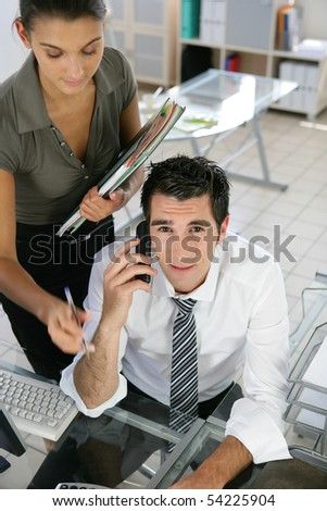 Portrait of a young woman with documents and a young man phoning