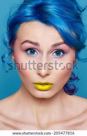portrait of a young woman with electric blue hair and eyes.