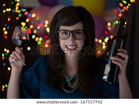 Portrait of a young woman with glasses holding a bottle and a glass of red wine. - stock photo