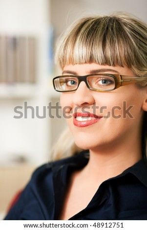 Portrait of a young woman with glasses sitting in front of a book shelf