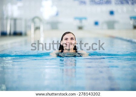 Portrait of a young woman with long hairs in swimming pool. Relaxing after fitness exercises. Indoor sport pool with blue water. - stock photo
