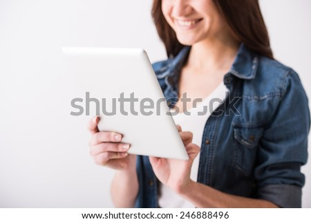 Portrait of a young woman with tablet on grey background. - stock photo