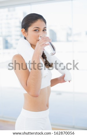 Portrait of a young woman with towel around neck drinking water in fitness studio - stock photo
