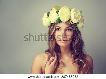 Portrait of a Young Woman with Wreath of Flowers on Gray Background. Natural Beauty Concept. Toned Photo with Copy Space. - stock photo